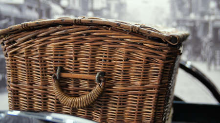 Basket in delivery retro car. Media. Vintage delivery service on European retro cars. Close-up of wicker basket behind car with retro body and steering wheel Stock fotó