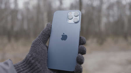 New York, USA - 11.11.2020: Hand in knitted glove holding Apple iPhone 12 Pro Max Action. Outdoors demonstration of the back logo and cameras. Sajtókép