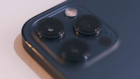 Bratislava, Slovakia - 11.12.2020: Details of a new Apple iPhone 12 Pro Max. Action. Close up of three cameras of a beautiful blue smartphone isolated on white background.
