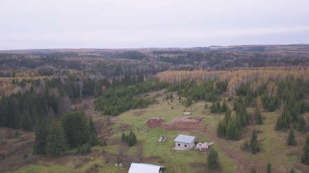 Russian village with summer old wooden houses surrounded by forests of northern Karelia, Russia. Clip. Aerial view of countryside landscape and endless Taiga on cloudy sky background.