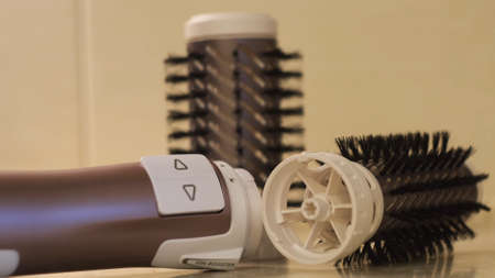 Close up of automatic dryer for hair styling, hairdresser tools and accessories. Concept. Hairdryer and nozzles: volume diffuser and round combs.