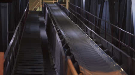 Machines working and conveyor line transporting sand. Stock footage. Conveyor belt with small pebble at the concrete mixing plant, factory equipment.
