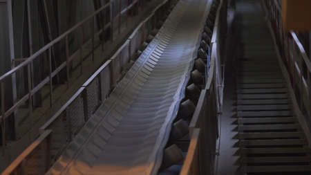 Moving conveyor belt line at the factory. Stock footage. Conveyor belt with sand at the plant of construction materials production, heavy industry concept. Stock fotó