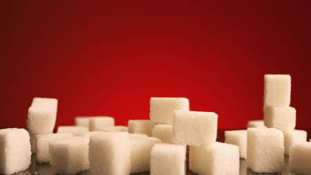 Close up of small sugar cubes falling down isolated on red background. Stock footage. Concept of sweets and unhealthy diet, pressed sugar falling down to a pile of white pieces.