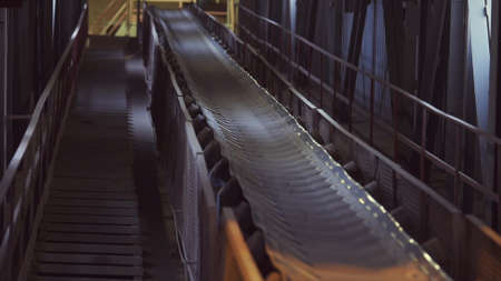 Conveyor belt in a factory of building materials production. Stock footage. Close up of production line with small crushed stones or gravel.