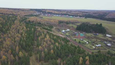 Aerial view from above over small village. Clip. Ecological place for agriculture activity and for the living located near mixed autumn forest and green field. Stock fotó