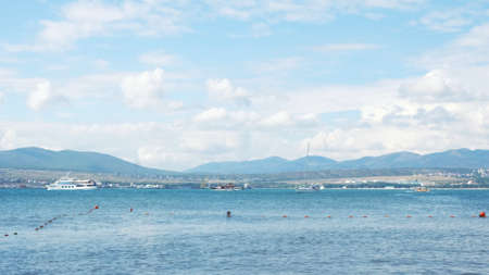 Mediterranean sea and the people on small touristic ships. Summer sunny day and rippled blue water where the yachts are moving slowly on endless horizon background with mountains and blue cloudy sky. Stock fotó