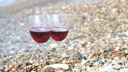 Two glasses of red wine on the pebble beach at the sea coast. Concept. Vacation pleasure and romantic date details, close up of two transparent glasses standing on stones near wavy shore.