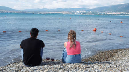 Young couple with wine having romantic date on a pebble beach. Concept. Rear view of a man and a woman with african braids sitting together and enjoying summer marine landscape. Stock fotó