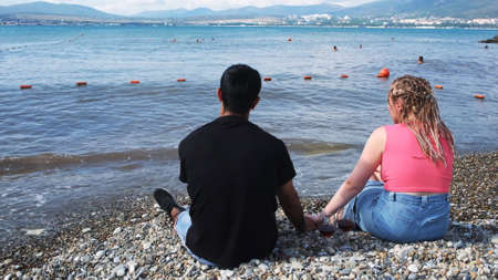 Couple holding hands while sitting on the pebbles near the sea. Concept. Rear portrait of young tourist couple together holding hands on pebble beach with two glasses of red wine. Stock fotó