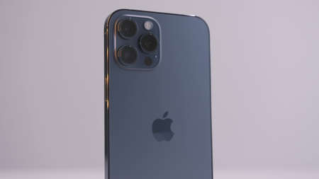 Beijing, China - 11.23.2020: Close up of a new iPhone 12 Pro Max in Pacific blue color. Action. Presentation of a new device with three cameras isolated on white background.