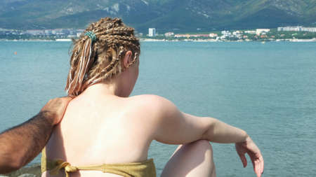 Male hand applying sunscreen on girlfriend back. Concept. Man hands applying sun protection cream on female with african braids on blue sea beach background, protection from sunburn.