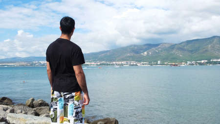 Rear view of a tourist by the sea. Concept. Happy man outdoor on edge of cliff enjoy the view of the turquoise sea and mountains far in the distance on blue cloudy sky background.