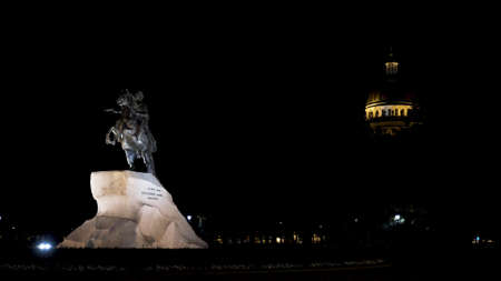 Statue of Peter the Great at night in Saint Petersburg, Russia. Monument of the Bronze Horseman on the Senate Square under the light of a street lamp on the background of Saint Isaac cathedral and black sky.
