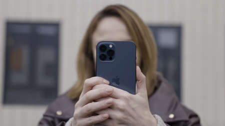 Vienna, Austria - 11.20.2020: female using a new phone of pacific blue color. Action. Close up of a pretty woman with a new Apple Iphone 12 Pro Max making a selfie or video phone call. Sajtókép