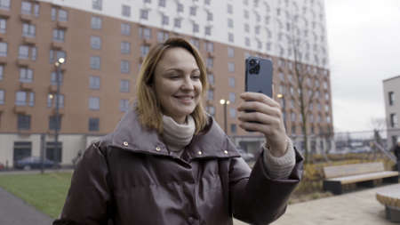 Moscow, Russia - 11.22.2020: Portrait of a happy woman making a selfie on a new Apple Iphone 12 Pro Max. Action. Female outdoors holding a new device of pacific blue color. Sajtókép