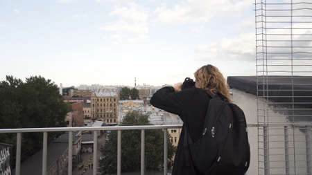Pretty young tourist taking photographs while sightseeing. Action. Woman walking in the street and photographing a beautiful panorama of a city from the roof of a building. Stock fotó