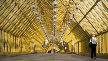 People walking inside pedestrian bridge in Moscow, Russia. Action. View inside of Andreyevskiy bridge with bright yellow metal beams and hanging lanterns.