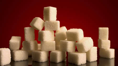 Close up of many sugar cubes standing on the top of each other isolated on red background. Stock footage. Concept of candy, sweets and food.