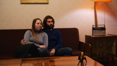 Interior of typical soviet style apartment with old furniture and retro design. Media. USSR family, man and woman sitting on a couch and watching TV.