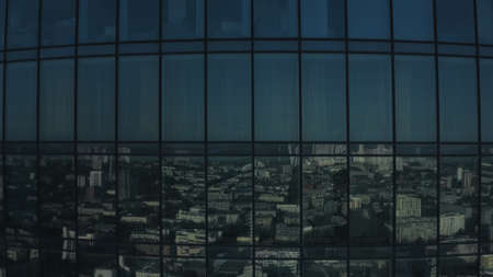 Aerial view of skyscraper office building with panoramic windows. Stock footage. Corporate building with glass facade and the reflection of the city.