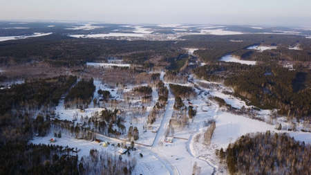 Classic village houses and the streets covered by deep fresh snow in winter, aerial view. Action. Small settlement located near pine forest on a sunny day.