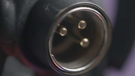 Close up of microphone trs connector on blurred purple background. Action. Details of instrumental equipment at the recording studio.