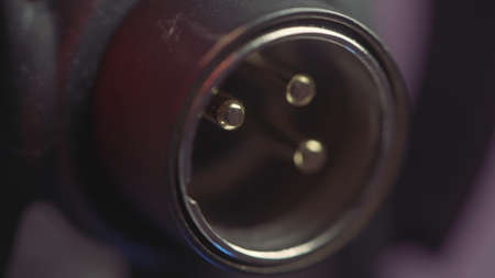 Close up of microphone trs connector on blurred purple background. Action. Details of instrumental equipment at the recording studio. Stock fotó