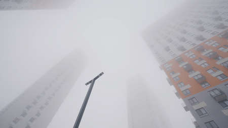 Residential high-rise buildings in fog. Action. Bottom view of high-rise buildings shrouded in thick fog. Cloudy weather with fog envelops high-rise buildings