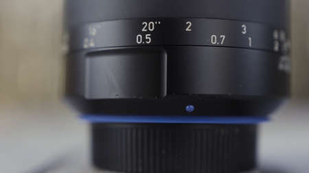 Close up of camera lens. Action. Details of black plastic photo and video new camera body on blurred background. Archivio Fotografico