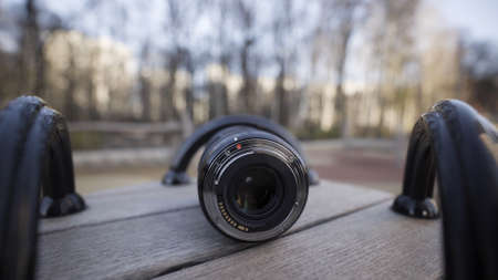 Close up front view of a black plastic camera lens on blurred background outdoors. Action. Demonstration of photographer equipment.