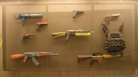 Weapons hang on wall. Stock footage. Colorful weapons of different types hang on wall. Wall with weapons for shooting. Wall with weapons for playing paintball or airsoft
