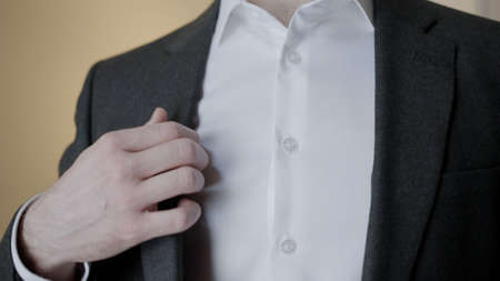 Close-up of gentleman adjusting suit jacket. Action. Attractive man adjusts tuxedo before celebration. Gentleman straightens jacket and buttons it up
