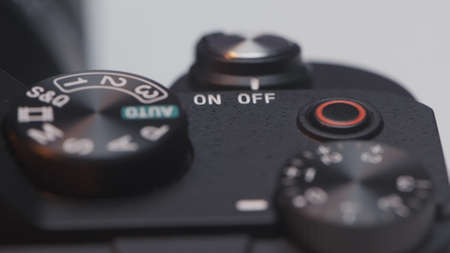 Close up of DSLR camera buttons and dials. Action. Details of a new professional camera on white background.