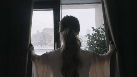 Rear view of a young woman with long curly hair opening curtains on window in the morning at home. Action. Silhouette of a girl in the dark room opening curtains.