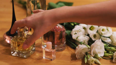 Small bottles with perfume and flowers on a wooden table. Concept. Close up of woman choosing a fragrance and taking one with her hand. Banco de Imagens