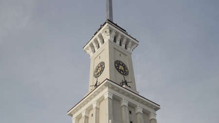 Bottom view of a clock tower with a long spire on blue cloudy sky background. Action. Details of an ancient historical building. Banco de Imagens
