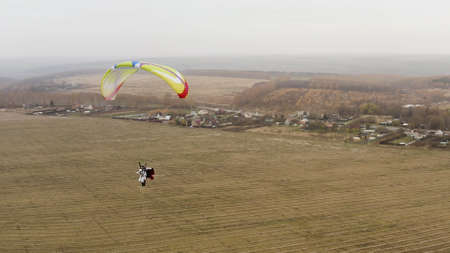 Beginning of paragliding, instructor  a red cloak and client rising into  air. Action. Paragliders soaring on cloudy sky background.