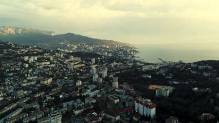 Aerial morning skyline over the city located by the sea. Shot. Breathtaking landscape with a early morning haze above the coastal town and calm water surface. Banco de Imagens