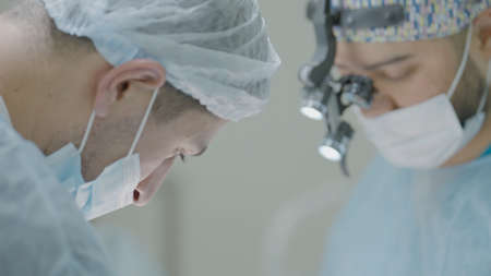 Two surgeons work together in operating room. Action. Couple of professional surgeons during operation. Bright operating room and surgeons at work Banco de Imagens