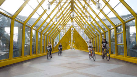 Moscow, Russia - July, 2020: Pedestrian bridge with cyclists. Action. Beautiful yellow bridge for pedestrians in city park. Group of cyclists rides on covered bridge for pedestrians