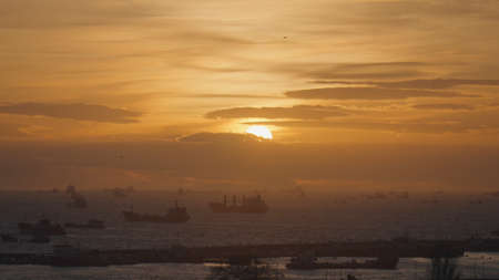 Various boats and ships moored near the sea port. Action. Aerial view of marine landscape with bright orange sunset above rippled water and ships, water transport concept.