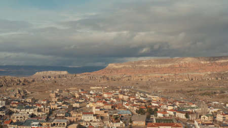Aerial panoramic view of a southern city under bright hot sun on a summer day. Action. Many small houses and narrow streets on dry mountains on the background.
