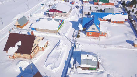 Aerial view of big and small brick houses on a winter sunny day. Clip. Ground is covered by clean white snow, concept of ecology.