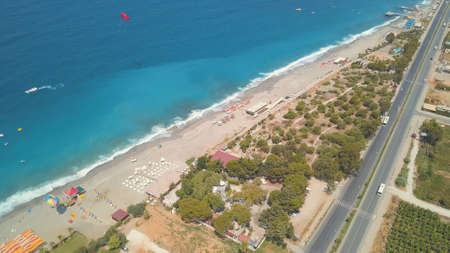 Aerial view of a tropical beach with white sand, green palm trees and blue sea. Clip. Touristic resort on a summer sunny day located by the city with a long road along the coast.
