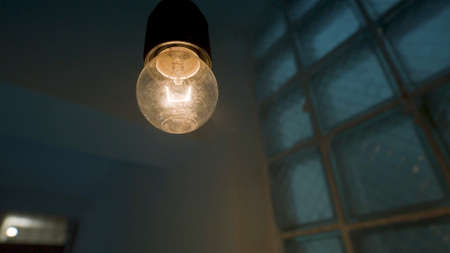 Light bulb and light flash in dark room. Stock footage. Frightening dark room with blinking bulb. Neon light and light bulb blink in dark room