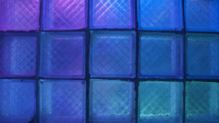 Square glass with neon light. Stock footage. Glass wall on background of flashing colored lights. Neon lights blink behind glass wall in nightclub