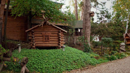 Details of a summer park with traditional russian fairytale wooden houses surrounded by green lawn and trees. Video. A hut on chicken legs or Baba Yaga hut In Slavic folklore.