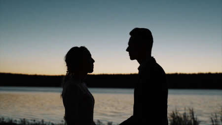 Silhouette of a couple in love at sunset in front of a river. Video. Side view of a man and a woman kissing during romantic date, concept of love.