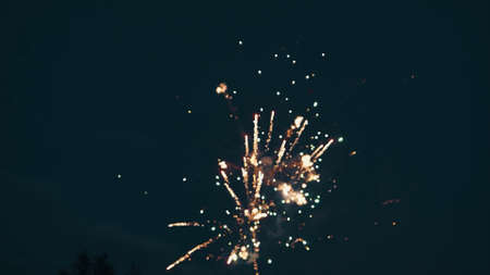 Bottom view of a dark blue night sky and exploding fireworks. Video. Blurred shining lights of fireworks, concept of celebration.